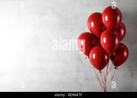 Bunch of red balloons on concrete wall background - Stock Image