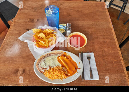 Mexican dinner plate with an enchilada, beans and rice with a basket of chips and salsa on a restaurant table top. - Stock Image