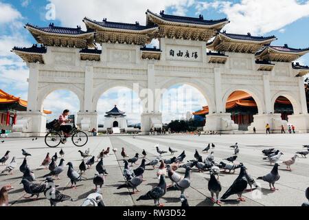 Taipei, Taiwan - November 06, 2018: Woman rides a bicycle in front of the National Chiang Kai-shek Memorial Hall on November 06, 2018 in Taipei, Taiwan - Stock Image