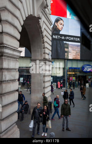 A model in an ad for clothing brand Net-a-Porter, looks down on passers-by, in Piccadilly Circus, on 7th March 2019, in London, England. - Stock Image