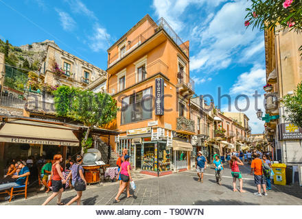 Busy section of Corso Umberto in Taormina, Italy on the Mediterranean island of Sicily on a warm summer day with crowds of tourists - Stock Image