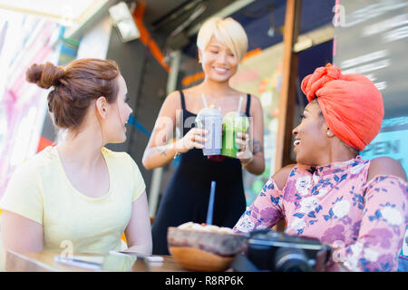 Waitress serving smoothies to women friends at sidewalk cafe - Stock Image