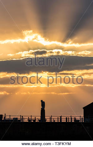 Morecambe, Lancashire, UK, 9 April 2019. UK Weather: A beautiful sunset over the Stone Jetty and Morecambe Bay as the clouds split the sunlight into distinct rays fanning out above the Mythical Bird Sculpture. The spectacular sunsets at Morecambe and the view of the Lake District Hills across the bay continue to attract tourists throughout the year. Credit: Keith Douglas News/Alamy Live News - Stock Image