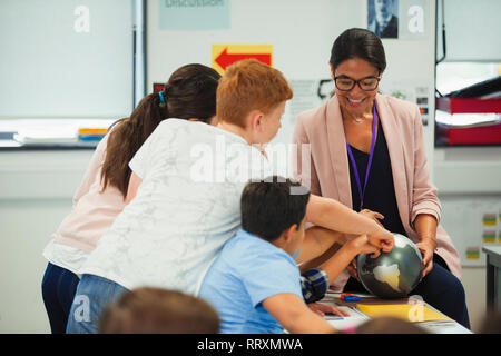 Junior high school students pointing at globe in geography teacher hands - Stock Image