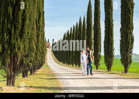 Castiglione d'Orcia, Orcia valley, Siena, Tuscany, Italy. A couple walking along a country road - Stock Image