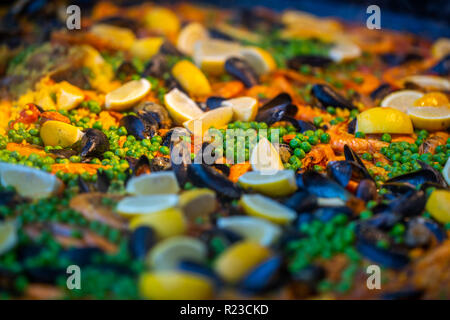 Spanish seafood paella with chicken, mussels, prawns, shrimps and chorizo sausages in traditional pan close up in a food market - Stock Image