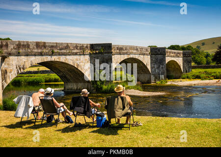 UK, Yorkshire, Wharfedale, Burnsall, visitors relaxing on village green at bridge over River Wharfe - Stock Image