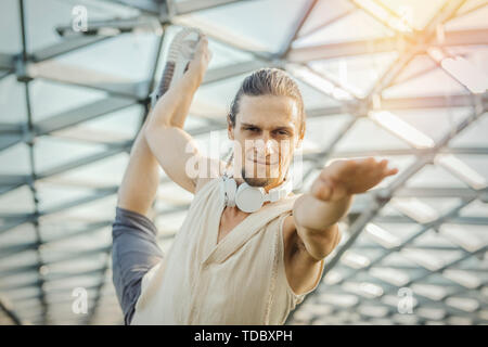 Close up of attractive athletic man practicing yoga and warming up outdoors in modern park under the glass dome. - Stock Image