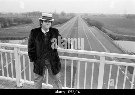 Elton John pictured standing on a bridge over the motorway. 5th December 1982. - Stock Image