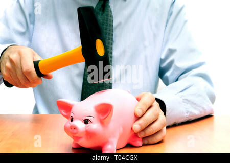 man breaking a piggy bank with a hammer - Stock Image