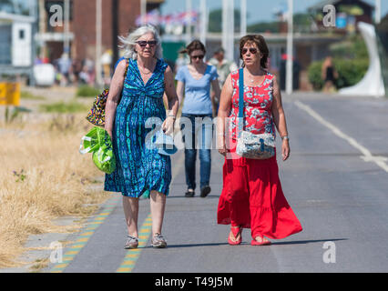 Front view of a pair of middle aged women walking together toward the camera along the seafront promenade in Littlehampton, West Sussex, England, UK. - Stock Image