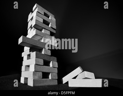 Tower of wooden blocks finely balanced,risk of collapsing - Stock Image