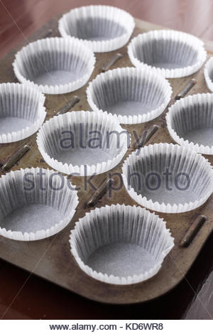 Empty white cup cakes papers ready for baking. - Stock Image