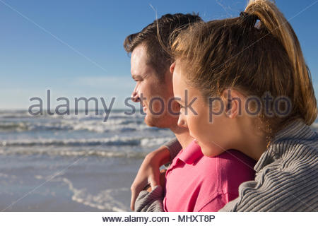 Romantic Couple Looking Out To Sea On Summer Beach Vacation - Stock Image