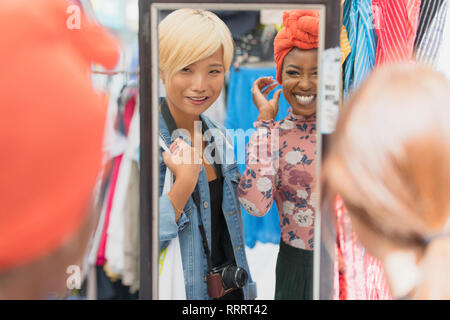 Young women friends shopping at mirror in clothing store - Stock Image