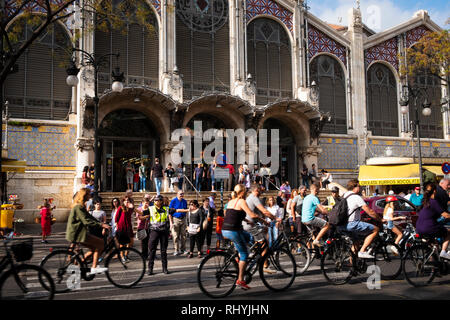 Police woman waving cyclists past the outside of the Central Market in Valencia Spain - Stock Image