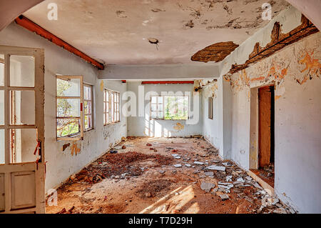 Interior of an old desolated house with white cracked walls and broken windows - Stock Image