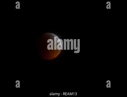 Glasgow, Scotland, UK. 21st January, 2019. Less than perfect skies still allowed views of the total lunar eclipse from Glasgow and the south west area of Scotland. This unusual event is also known as a Blood moon as the light from the sun bending round the earth's circumference causes the moon to turn orange/red. Credit: Douglas Carr/Alamy Live News - Stock Image