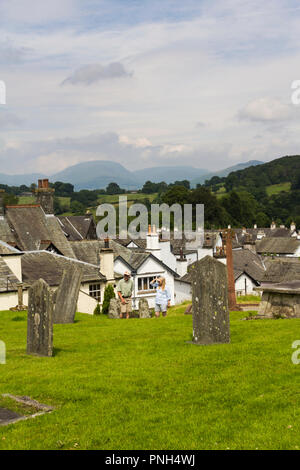 Visitors approaching the parish church of St. Michael and All Angels overlooking the village of Hawkshead in Cumbria. - Stock Image