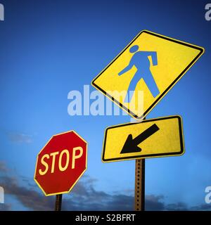Conceptual crossing pedestrian and Stop signs - Stock Image