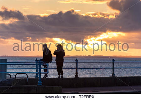 Morecambe, Lancashire, UK, 2 April 2019. UK Weather: A beautiful sunset over Morecambe Bay from the Stone Jetty. The spectacular sunsets at Morecambe have been an enduring attraction for visitors over many decades. Credit: Keith Douglas News/Alamy Live News - Stock Image