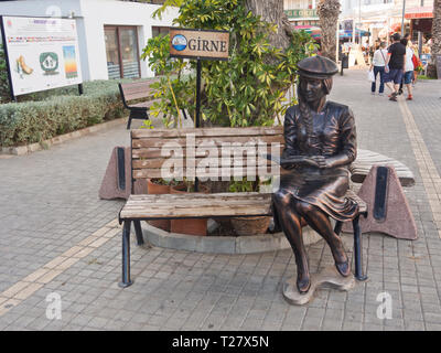Fun bronze sculpture of a reading girl placed in a popular tourist pedestrian street in Kyrenia ( Girne ) in northern Cyprus - Stock Image