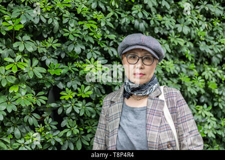 Fashionable Taiwanese woman of Chinese ethnicity against backgorund greenery - Stock Image