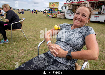 Seated woman smiling and relaxed before a muddy obstacle course run - Stock Image