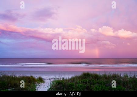Rainbow over the Atlantic Ocean Hilton Head Island South Carolina with a path through the dune grass leading to - Stock Image
