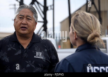 Hawaii Department of Transportation Kahului Harbor District Manager Duane Kim speaks with Petty Officer 2nd Class Kim Fennick during a post-hurricane port assessment of Kahului Harbor in Kahului, Hawaii, Aug. 25, 2018. Coast Guard assessment teams are working to ensure ports are safe to reopen following Hurricane Lane. Coast Guard photo by Petty Officer 1st Class Patrick Kelley. - Stock Image