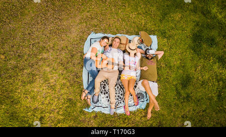 Top vertical aerial view of group of friends lay down on the meadow and enjoy the friendship playing a guitar and relaxing all together - people  frie - Stock Image