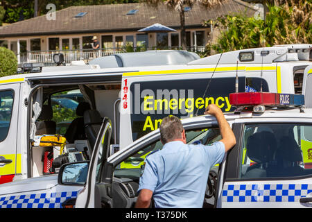New South Wales police officer stood by police car and health ambulance at Palm beach,Sydney,Australia - Stock Image