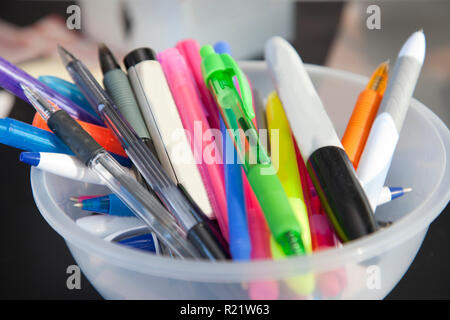 Pens, highlighters and permanent markers fill a bowl of writing utensils at home or office - Stock Image