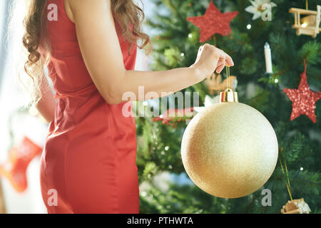 Closeup on trendy woman in red dress with big gold Christmas ball near Christmas tree - Stock Image