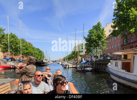 Tourists' sightseeing cruise boat on the Christianshavns Kanal, Overgaden, Christianshavn, Copenhagen, Zealand, Denmark - Stock Image