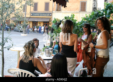 Girls in the town of Cagli in Le Marche, Italy, meet for an evening drink and chat at the bar in the piazza - Stock Image