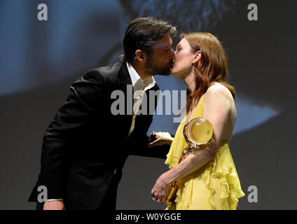 Karlovy Vary, Czech Republic. 28th June, 2019. Scriptwriter and director Bart Freundlich kisses his wife US actress Julianne Moore, as she received Crystal Globe award for contribution to world cinematography at the opening ceremony of the 54th Karlovy Vary International Film Festival in Karlovy Vary, Czech Republic, on Friday, June 28, 2019. Credit: Katerina Sulova/CTK Photo/Alamy Live News - Stock Image