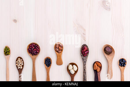 Assortment of beans and lentils in wooden spoon set up on wooden background. mung bean,soybean, red kidney bean - Stock Image