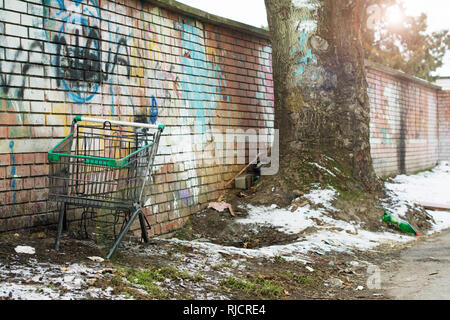 Rejected shopping cart without wheels is standing by a naked wall and a tree on a cold, sunny winter day. - Stock Image