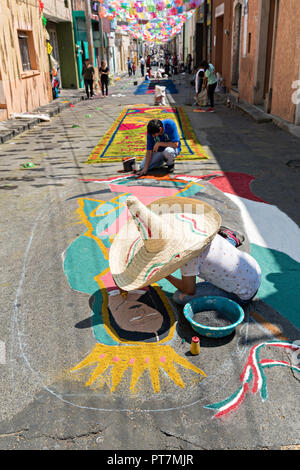 A young man wearing a giant sombrero hat creates a giant floral carpet made from colored sawdust and decorated with flowers during the 8th Night Celebration marking the end of the Feast of St Michael in the central Mexican town of Uriangato, Guanajuato. Every year the town decorates 5km of road with religious icons in preparation for the statue of the patron saint to be paraded through the town. Uriangato became an international sensation after wowing Brussels with their floral carpet displayed at the Brussels Grand-Place during the Belgium Floral Carpet festival. - Stock Image