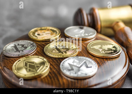 Different cryptocurrencies and gavel over gavel wooden board.Concept image for cryptocurrency - Stock Image
