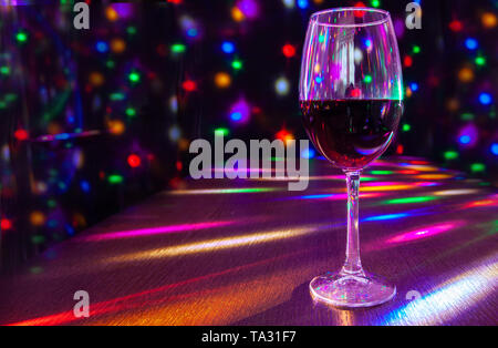 glass of wine on the table in the restaurant with bright festive lighting closeup - Stock Image