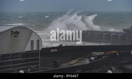 Brighton, UK. 12th Mar, 2019. Waves crash over Brighton Marina western wall this morning as Storm Gareth starts to batter Britain and Ireland with winds expected to reach over 70mph in some parts Credit: Simon Dack/Alamy Live News - Stock Image