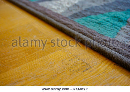 Close up of a blue carpet edge laying on a wooden floor. - Stock Image