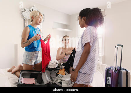 Young women friends packing for spring break in apartment bedroom - Stock Image