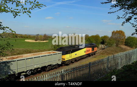 A GBRF, diesel locomotive propels its train of empty stone wagons off the branch line to the Hanson aggregate depot at Ashton in Makerfield. Cw 6688. - Stock Image