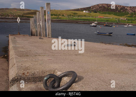 A view down a slipway at a harbour in a remote part of Scotland with wild landscape in the background and metal rope ties and a line of wooden posts - Stock Image