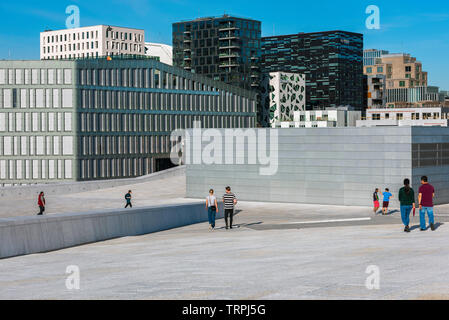 Opera House Oslo, view in summer of people descending the vast access ramp leading to the roof of the Oslo Opera House, with Barcode Buildings beyond. - Stock Image