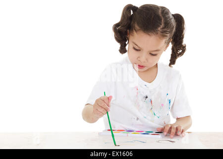 Stock image of female preschooler playing with watercolors over white background - Stock Image
