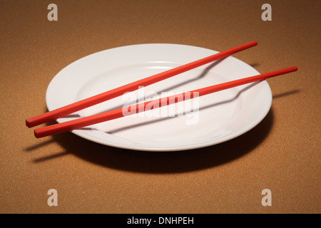 A pair of red chopsticks on a empty white dinning plate. - Stock Image